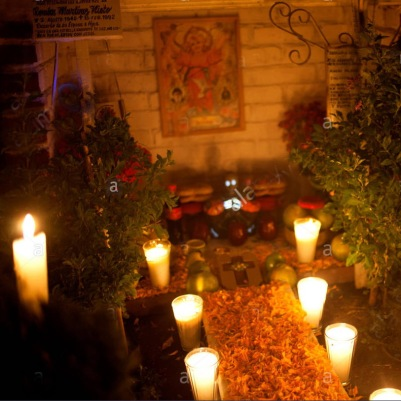 a-boy-sits-in-a-tomb-decorated-with-candles-and-yellow-marigold-flowers-FE5P1R